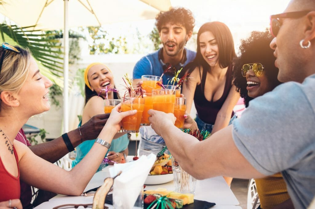 Young multiracial friends toasting beer at barbecue garden party
